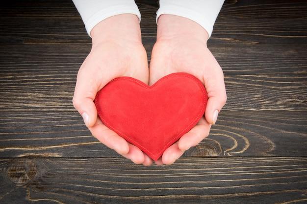 Красное сердце в руках женщины