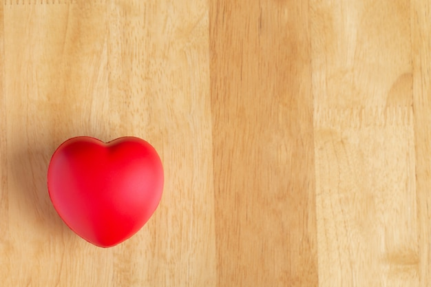 Red heart is placed on wooden floor