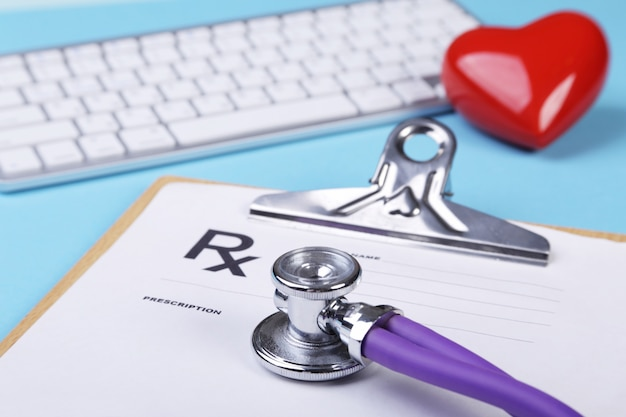 Red heart, keyboard and medical stethoscope lying on cardiogram chart closeup. medical help, prophylaxis, disease prevention or insurance concept. cardiology care.