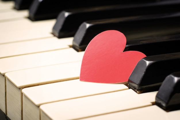 Red heart on a keys of a keyboard of an classic old piano.
