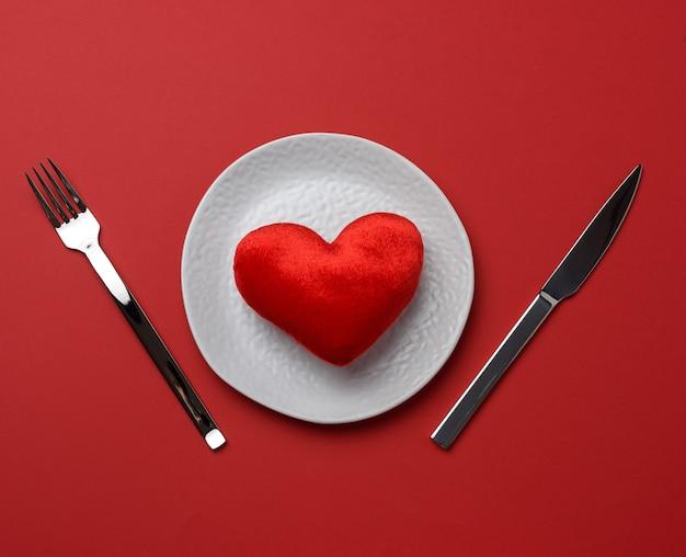 Красное сердце лежит в белой керамической тарелке на красном фоне
