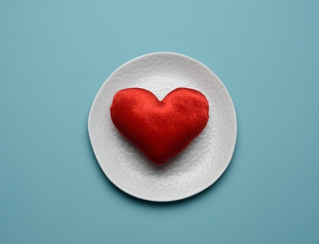 Red heart lies in a white ceramic plate on a blue background, top view