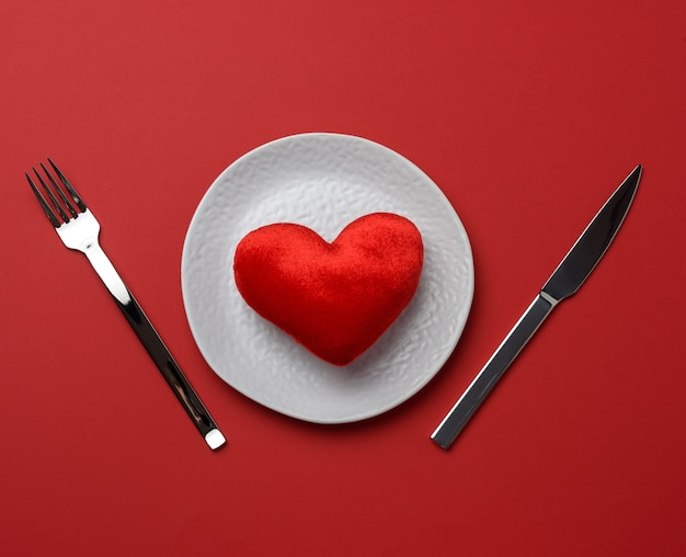 Red heart lies in a white ceramic plate on a red background