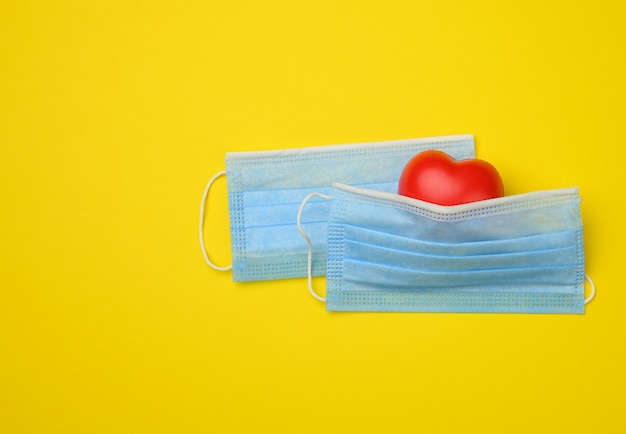 Red heart lies on a white disposable medical mask, yellow background, copy space