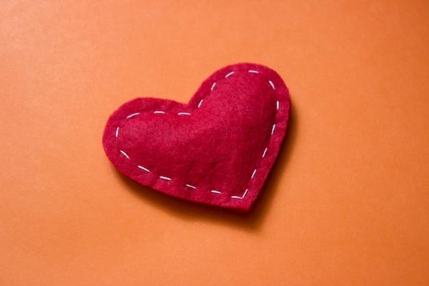 オレンジ色の背景に白い糸で生地で作られた赤いハート。愛、恋愛の概念。刺し繡のラインで明るい心を感じました。