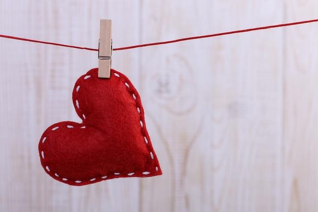 ピンでロープにぶら下がっている手作りのフェルトで作られた赤いハート