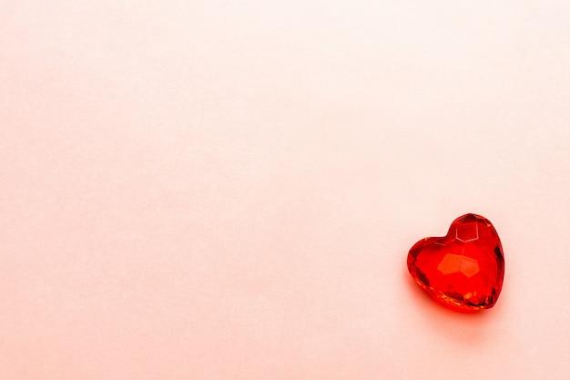 柔らかいピンクの紙に透明なカットガラスまたは多面的な石で作られた赤いハート