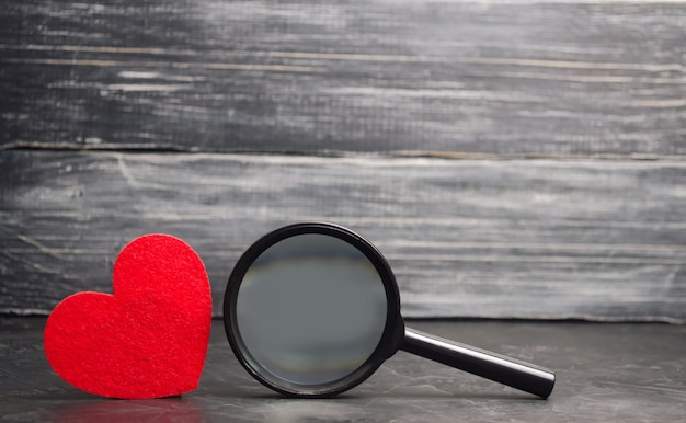 Red heart and magnifying glass. concept of love and relationships