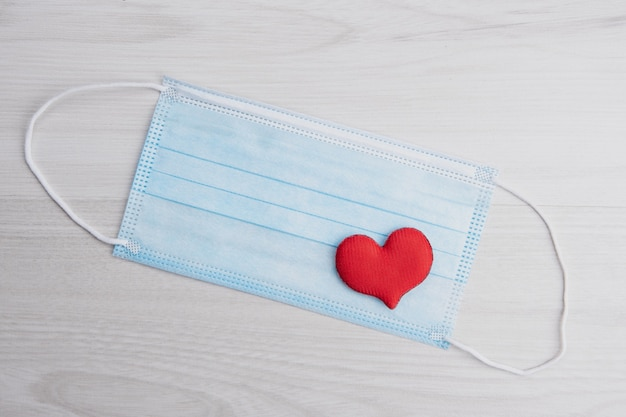 Red heart on medical face masks. concept support, love, care and a thank you to the frontline essential workers and healthcare.