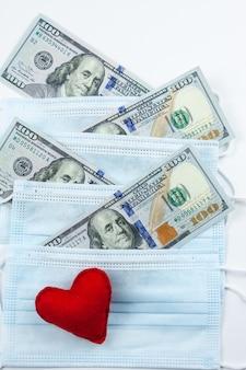 붉은 마음, 의료 마스크 및 달러. 코로나 바이러스로 인한 금융 위기. 비싼 병원 서비스.