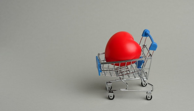 Red heart in a miniature metal trolley from the store on a gray surface. organ donation, transplant concept, banner