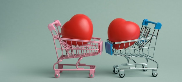 Red heart in a miniature metal trolley from the store on a gray surface. organ donation, transplant concept