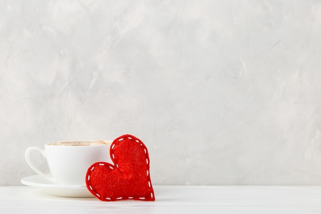 Red heart, morning coffee against the of a light wall, concept, a postcard for valentine's day.