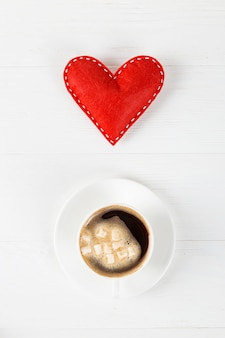 Red heart, morning coffee against the of a white table, concept, a postcard for valentine's day.