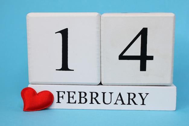 Красное сердечко рядом с календарем с датой 14 февраля. концепция дня святого валентина. понятие любви.