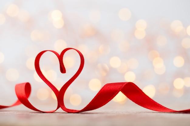 リボンの赤いハート。バレンタインデーの背景。