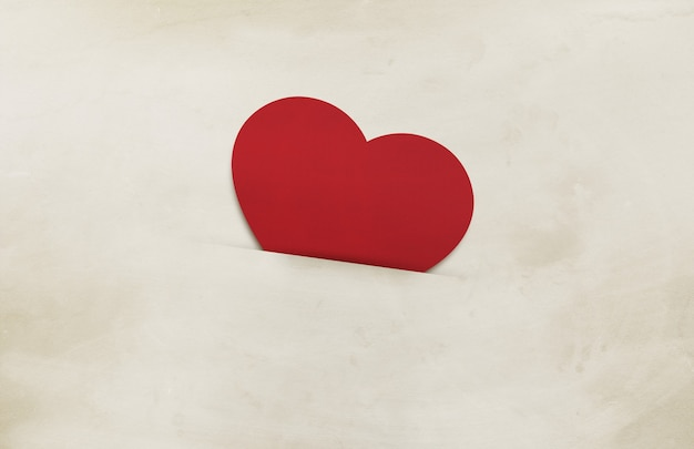 Red heart on old brown paper background