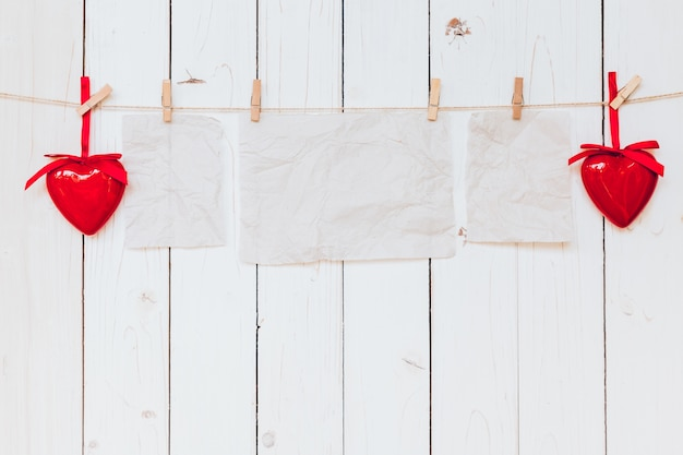 Red heart and old paper blank hanging at clothesline on wood white background with space. valentine day.
