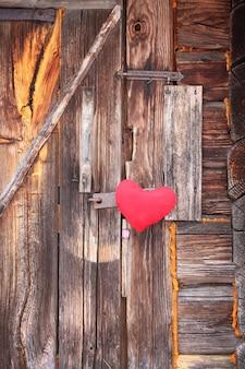 Red heart on old wooden door.