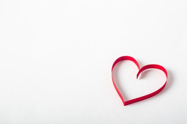 明るい白の背景に赤いハート。作曲バレンタインデー。バナー。フラットレイ、上面図。