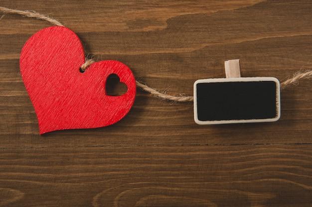 Красное сердце на веревке и небольшой доске