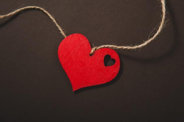 Красное сердце на веревке на черном фоне