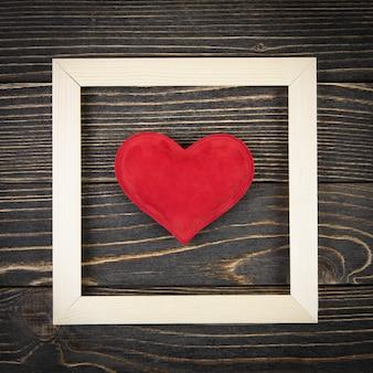 Красное сердце на старой деревянной поверхности