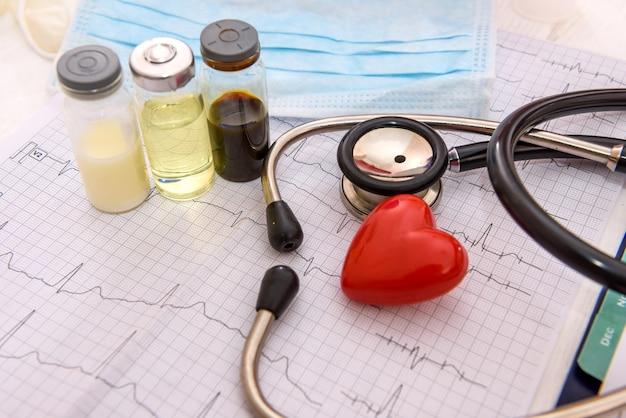 Красное сердце на кардиограмме с ампулами и стетоскопом