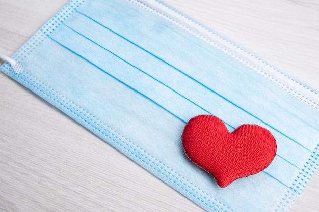 Красное сердце на медицинских масках для лица. концептуальная поддержка, любовь, забота и благодарность передовым работникам и работникам здравоохранения. с днем святого валентина. пандемия, карантинный коронавирус. день святого валентина.
