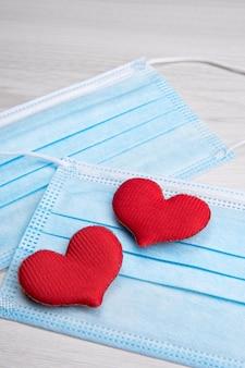 Красное сердце на медицинских масках для лица. концептуальная поддержка, любовь, забота и благодарность основным работникам и работникам здравоохранения. с днем святого валентина. пандемия, карантинный коронавирус. день святого валентина.