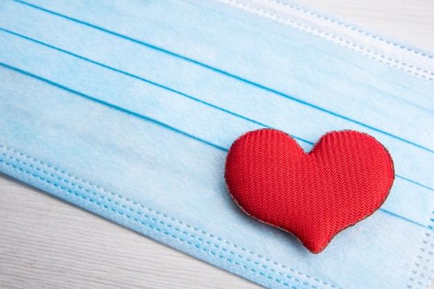 Красное сердце на медицинских масках для лица. концептуальная поддержка, любовь, забота и благодарность основным работникам и работникам здравоохранения.