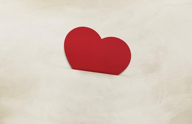 Красное сердце на фоне старой коричневой бумаги Premium Фотографии