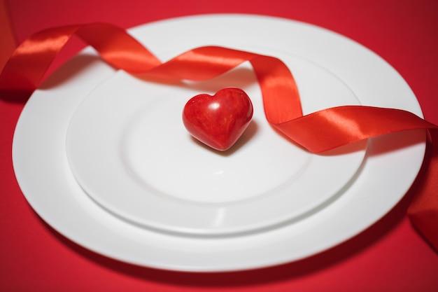 赤い背景のプレート上の赤いハート。バレンタイン・デー