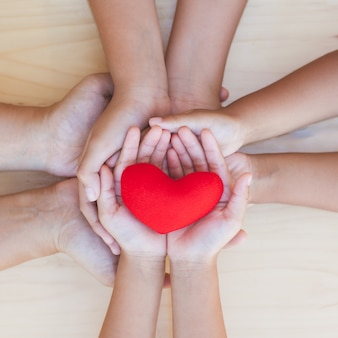 Red heart in parent and children holding hands together on wooden background.
