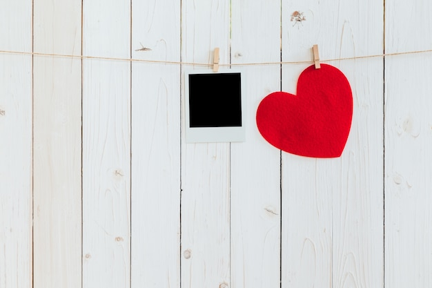 Red heart and photo frame blank hanging at clothesline on wood white background with space. valentine day.