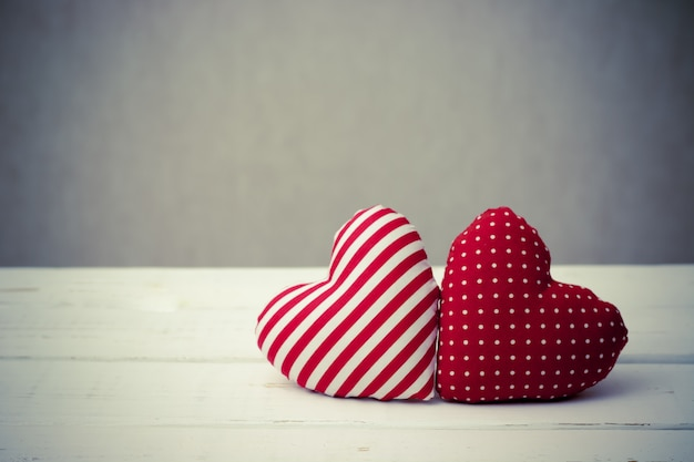 Red heart pillow on wooden table. valentine's day concept. vintage effect style.