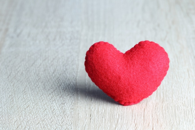 Red heart placed on wooden floor and have copy space for design.