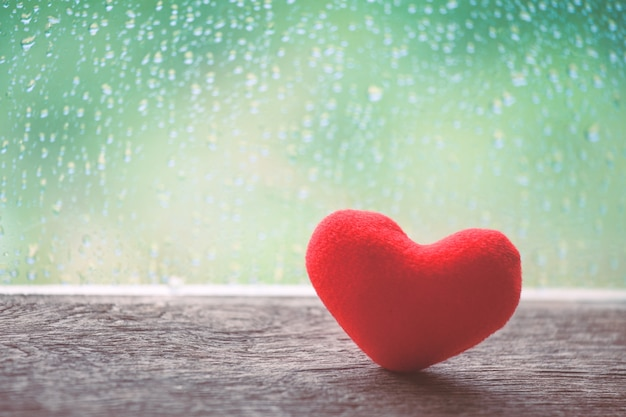 Red heart on rainy day window background in vintage color tone
