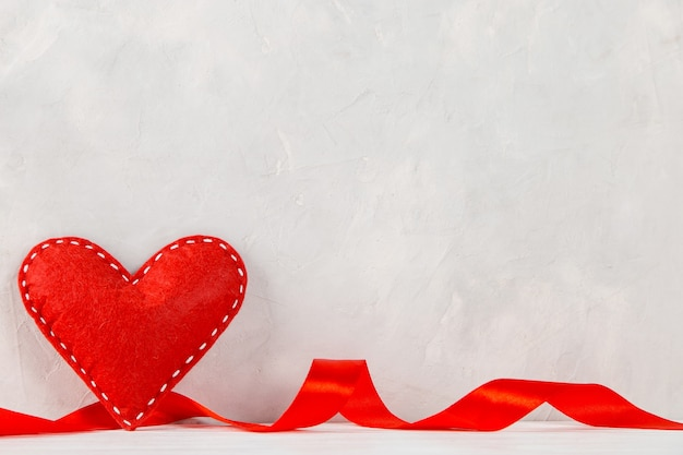 Red heart, ribbon against the of a white wall, concept, a postcard for valentine's day.