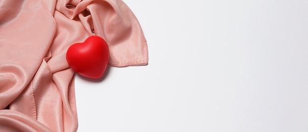 Резина красного сердца на белой предпосылке с космосом экземпляра. кардиология и концепция страхования.