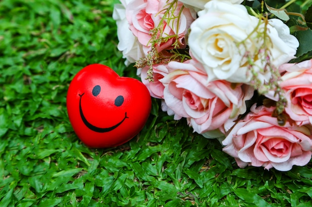 Red heart seem happy and bouquet of roses on green grass