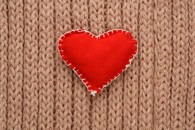 Red heart sewn from fabric on a knitted surface.