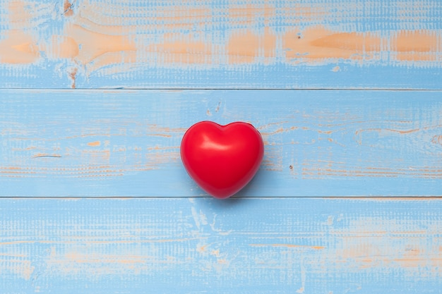 Red heart shape on blue pastel color wooden background.