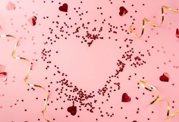 Красное сердце формы конфетти сердце вид сверху квартира лежала на розовом фоне. копировать пространство