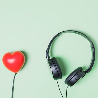 Red heart shape connected to headphone on turquoise background