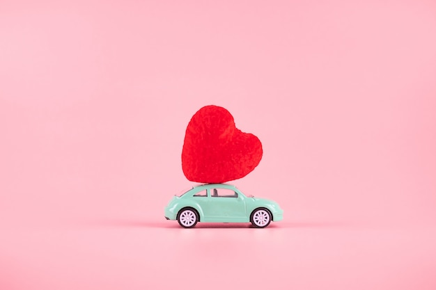 Red heart shape decoration on mini car toy with copy space for text on pink . love, wedding, romantic and happy valentine day holiday concept