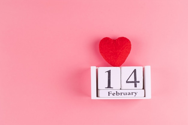 Red heart shape decoration with 14 february calendar on pink . love, wedding, romantic and happy valentine day holiday concept