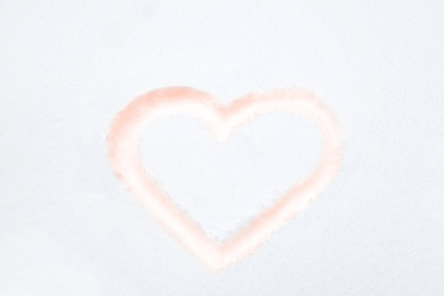 愛のバレンタインの背景として白い雪に描く赤いハートの形