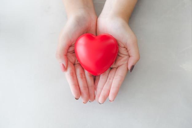 아름 다운 여자 손에 붉은 심장 모양 고무 프리미엄 사진