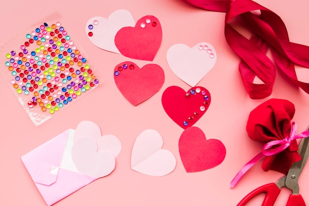 Red heart shape with ribbons on pink background